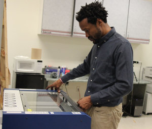 Dr. Eric Saliim working the Epilog Laser, which can cut through plastic, wood, glass and more. Photo by Tia Mitchell/Assistant editor.
