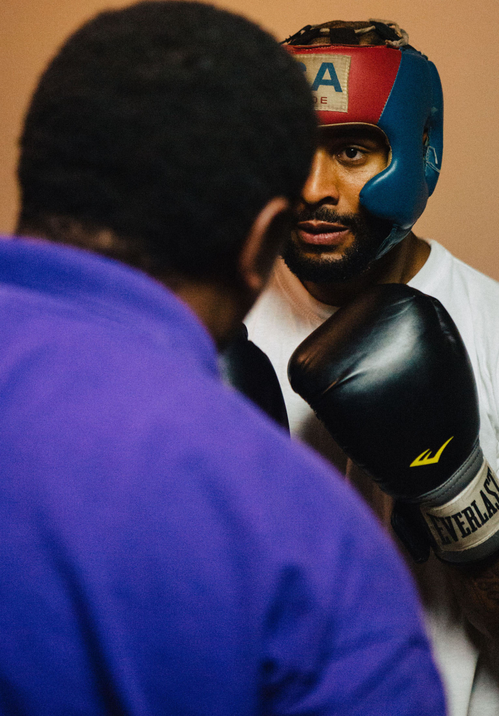 David Johnson, 28, concentrates on his form while preparing for combination punches with Bishop Arnold Harris. Bishop Harris helps David with words of encouragement. Photo by Bruce dePyssler/ Campus Echo Advisor